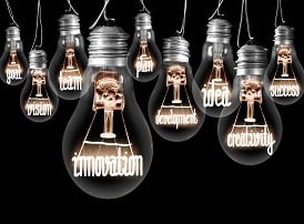 Photo of light bulbs with shining fibres in a shape of INNOVATION, concept related words isolated on black background